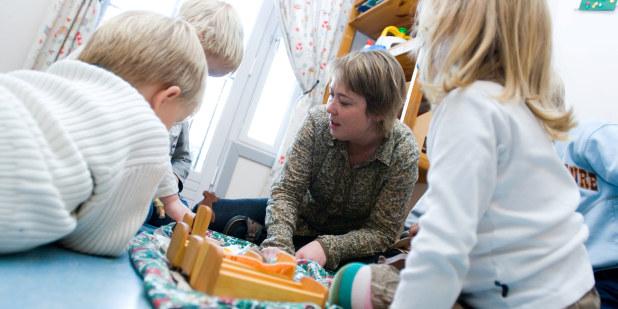 Barnehagebarn i lek sammen med en barnehagelærer.