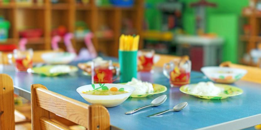 Bilde av matbord i barnehage, blå bordplate. Tallerkener og glass i plastikk, bestikk ligger ved siden av.
