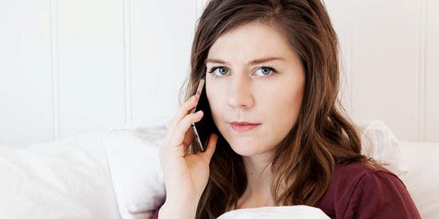 Dame i seng sitter i telefonen