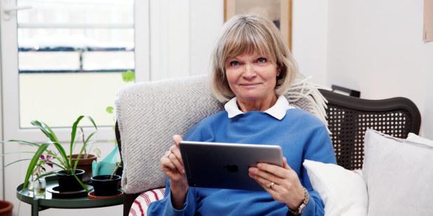 Voksen dame bestiller forsikring på nettbrett