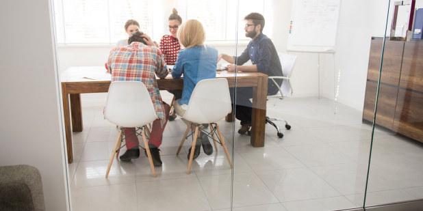 En gruppe mennesker sitter rundt et møtebord.