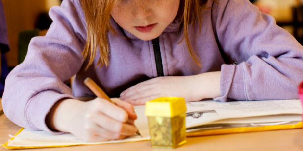 Bilde av elev som skriver i en bok.