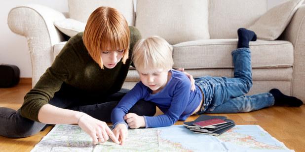 Bilde av mor og sønn som finner nytt reisemål på kartet