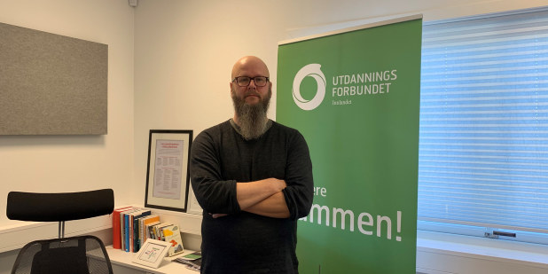 Bilde av en stående Thore Johan Nærbøe, fylkesleder i Utdanningsforbundet Innlandet, på kontoret sitt. Holder hendene i kryss foran på brystet.