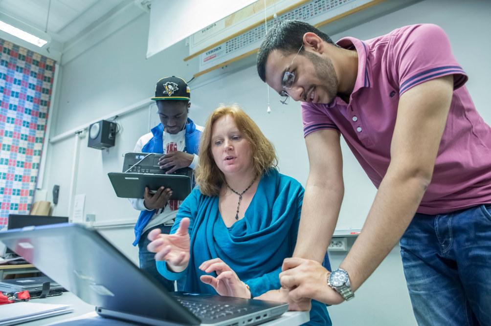 Kvinnelig lærer sitter ved en PC og forklarer noe til en ung mann som står og ser på skjermen. I bakgrunnen står en ung mann og venter på tur for å snakke med læreren.