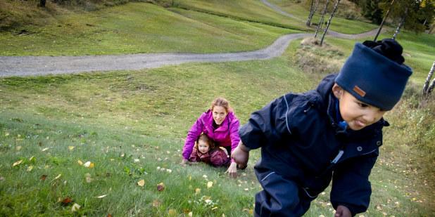 Barn som går opp en gresslagt bakke.