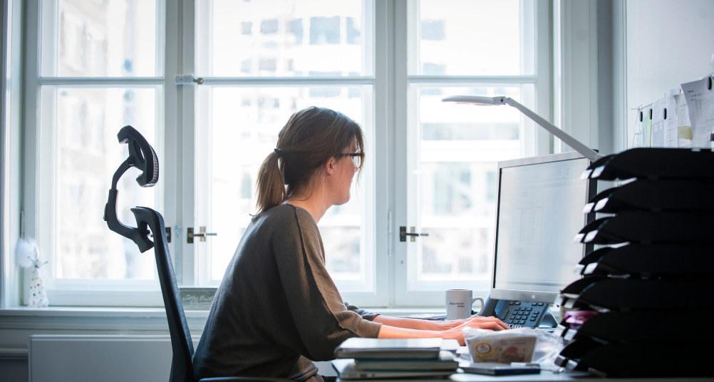 Kvinne sitter foran en PC og arbeider. Hun er på et kontor eller hjemmekontor.