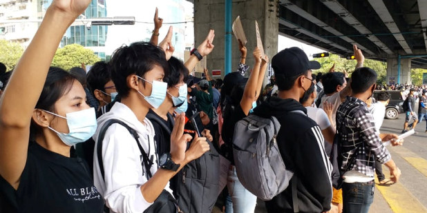 Mennesker i Myanmar protesterer mot militærkuppet ved å holde tre fingre opp i været.