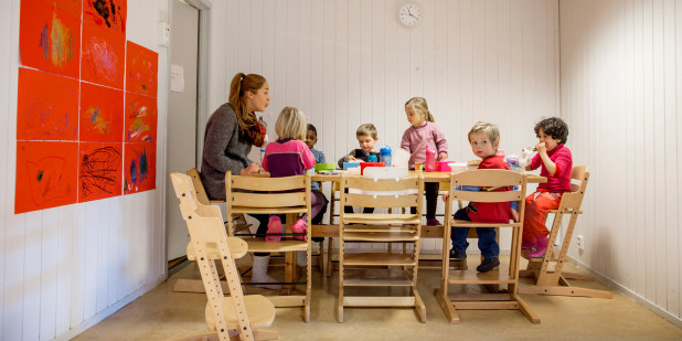 Barnehagebarn som sitter rundt et bord og spiser.