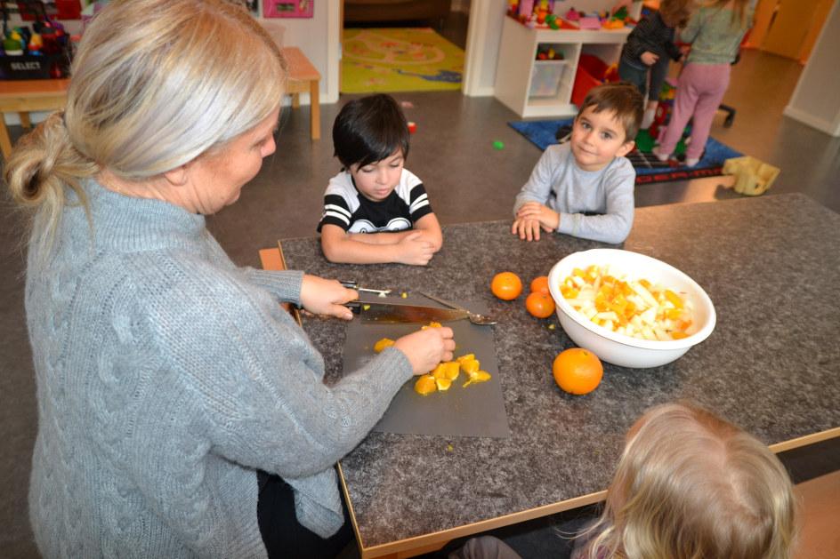 En lærer som kutter opp appelsin til tre barn i barnehagen.