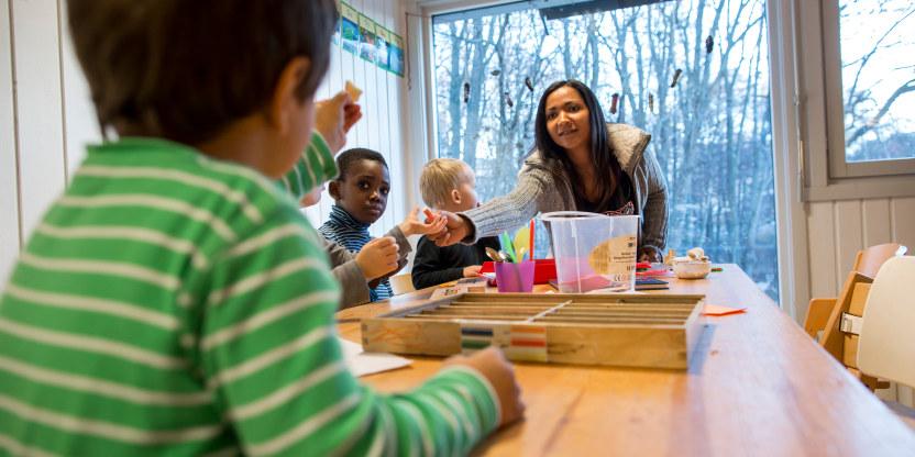 Barnehagebarn og en voksen sitter rundt et bord i en barnehage.