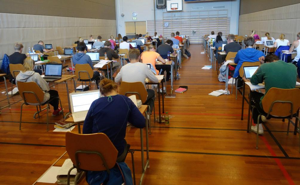 Elever har eksamen i en gymsal. De sitter ved hver sin pult med pc og jobber konsentrert med oppgaver. Bildet viser elevene bakfra.