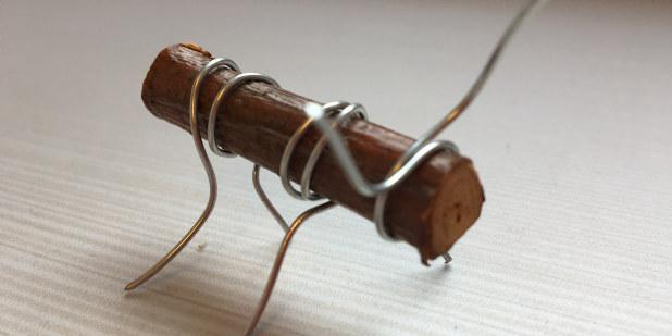 En leke eller liten skulptur som er laget av tre og metalltråd.