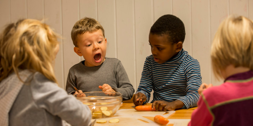 Fire barnehagebarn sitter rundt et bord. Et av barna ser med skrekkblandet fryd på grønnsakene som ligger på bordet.