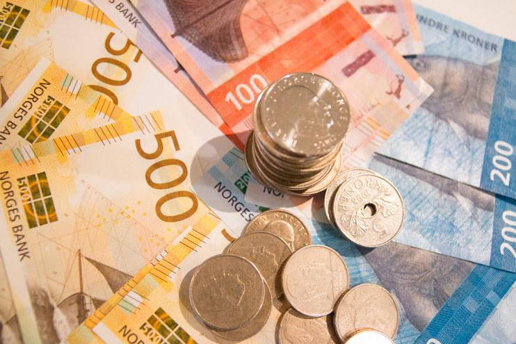 Bilde av norske sedler og mynter.