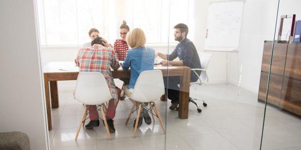 Bilde av fem personer som sitter rundt et møtebord inne på et møterom.