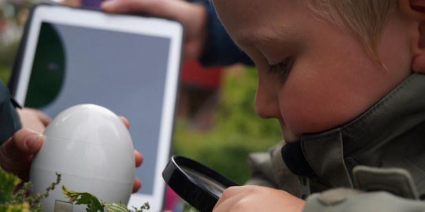 Et barn studerer gress i naturen gjennom et forstørrelsesglass.