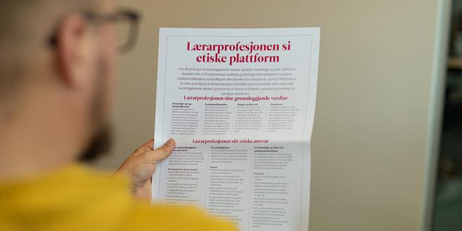 Mannsperson sitter og leser en plakat av lærerprofesjonens etiske plattform.