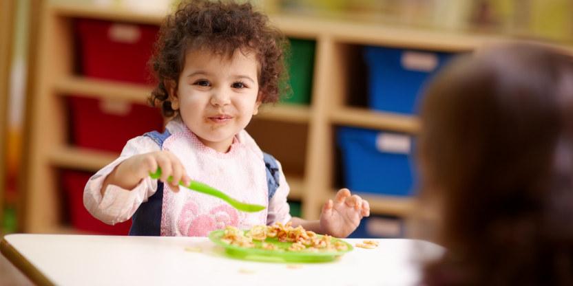 barnehagebarn  i godt humør som spiser ved bordet i barnehagen. bakhodet av voksen synes.