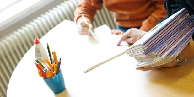 Deler av en elev som sitter ved et bord  og gjør skoleoppgaver.