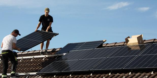To ungdommer som legger solcellepanel på et tak.