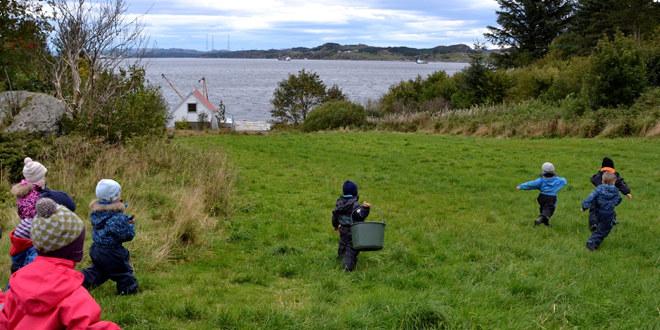 Barnehagebarn på en grønn slette eller svak hellende bakke, ned mot havet.