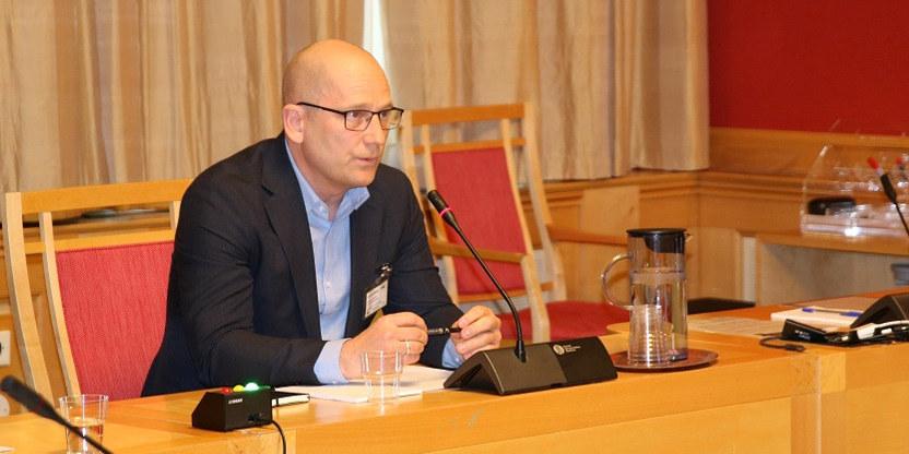 Utdanningsforbundets leder, Steffen Handal, sitter på stol med bordmikrofon foran seg.