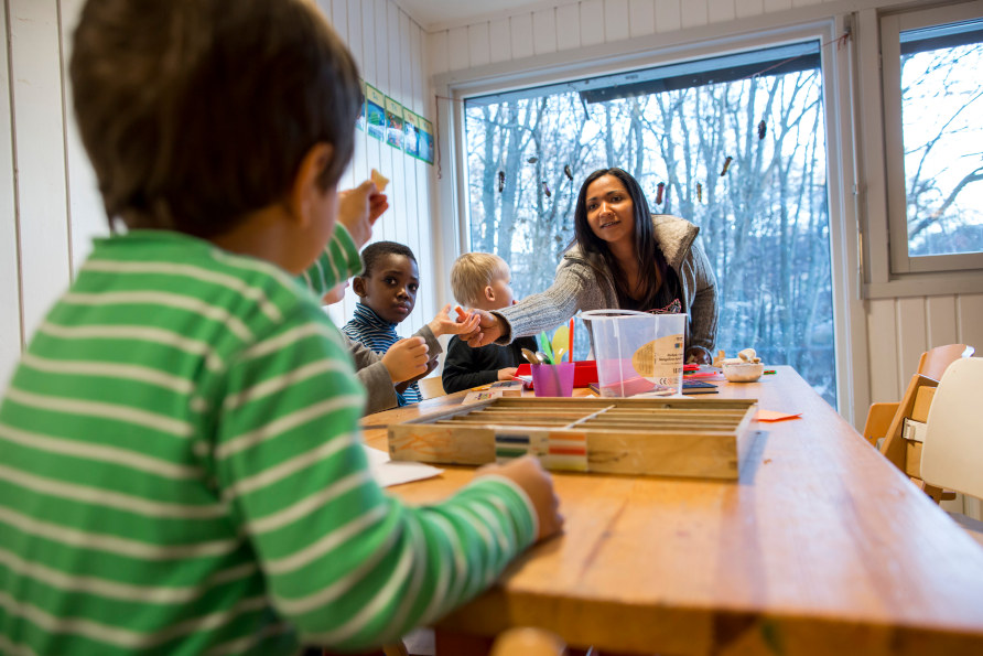 En kvinnelig barnehagelærer står ved enden av et bord der det sitter flere barnehagebarn rundt. Hun gir noe til et av barna.