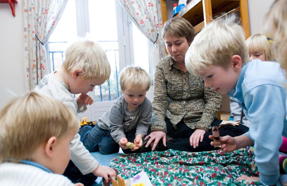 Barn sitter rundt en kvinnelig barnehagelærer på gulvet i en barnehage og leker.