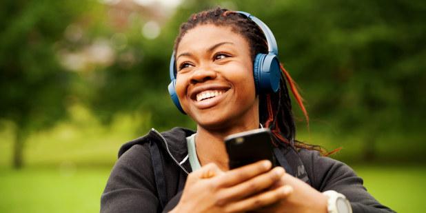 Jente som sitter ute med høretelefoner og telefon
