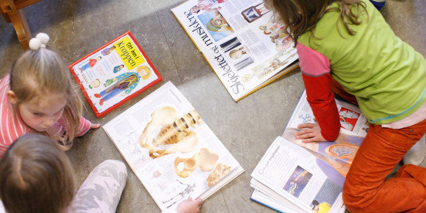Barn som leser bøker om kroppen.