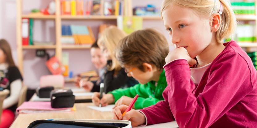bilde av jente med lyst  hår i et klasserom og andre elever i bakgrunnen