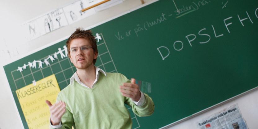 En yngre lærer står foran en tavle og underviser en forsamling.