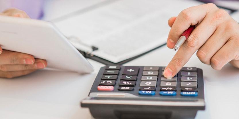 En person trykker med fingeren på en kalkulator.