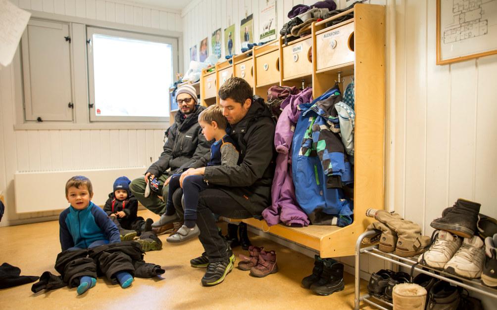 Et barnehagebarn  sitter på fanget til en voksen mann og blir kledd på yttertøy i garderoben i en barnehage. I bakgrunnen  ser vi en annen voksen mann og  flere barn.