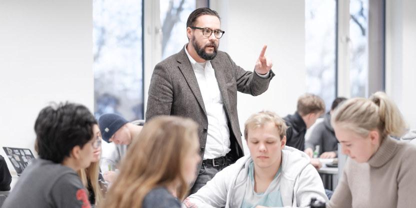 En mann med skjegg og briller står i et klasserom med flere videregående elever.