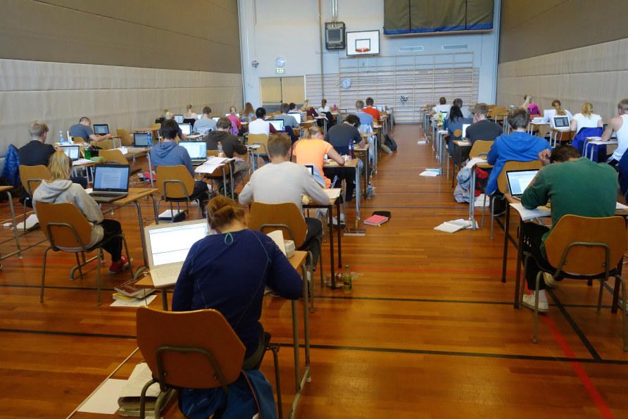 Mange elever sitter ved hver sin pult i en gymsal og gjennomfører eksamen.