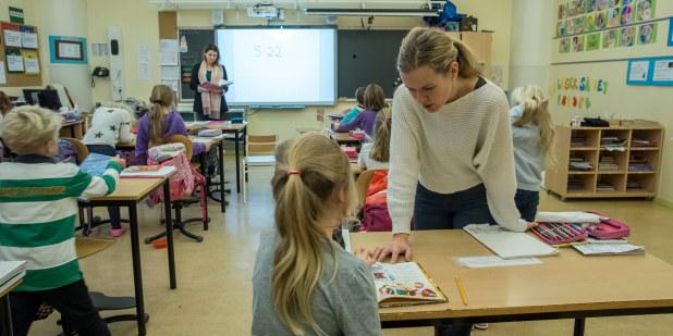 Bilde fra klasserom der en lærer hjelper en elev som sitter ved pulten sin.
