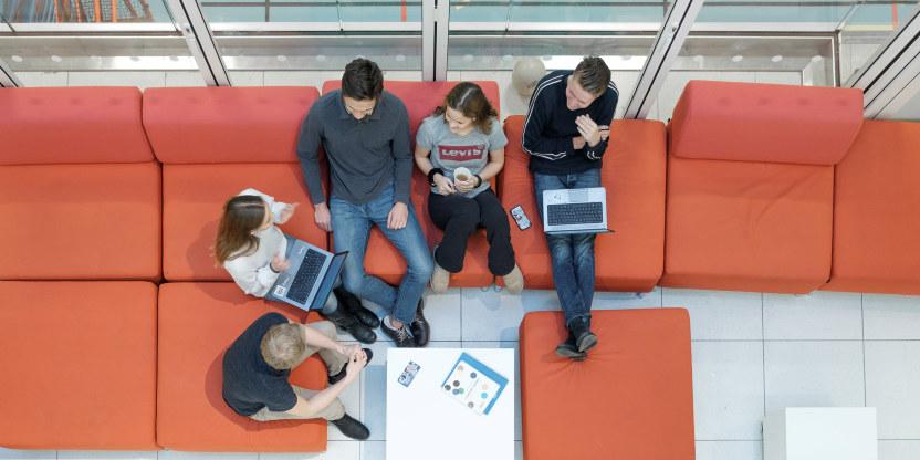 Bilde tatt ovenfra av tenåringer som sitter i en rød sofa.