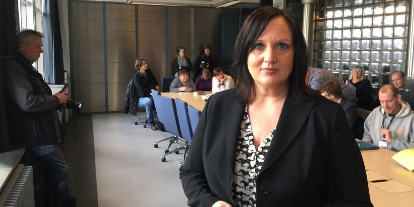 Forhandlingsleder for Unio Oslo, Aina Skjefstad Andersen, stående i et møterom i Oslo rådhus. Flere personer sitter på bordet bak henne.
