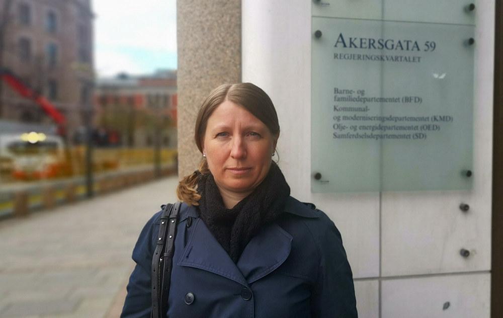 """Guro Elisabeth Lind ser alvorlig i kameraet. I bakgrunnen står et skilt med Akersgata 59 og """"Regjeringskvartalene"""" på."""