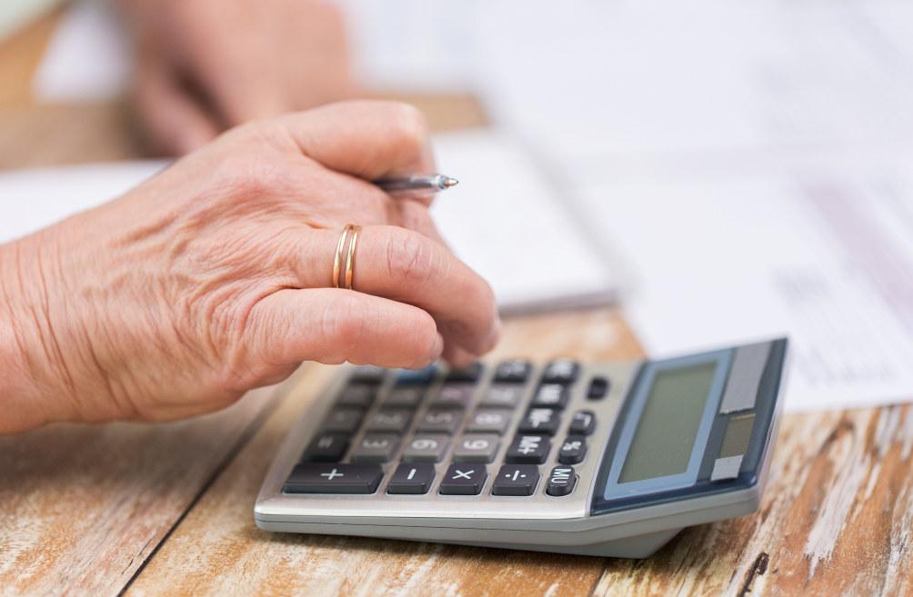 En hånd med giftering på som taster på en kalkulator på en bordplate. Hånden holder også en penn og i bakgrunnen ser vi ark på bordet.