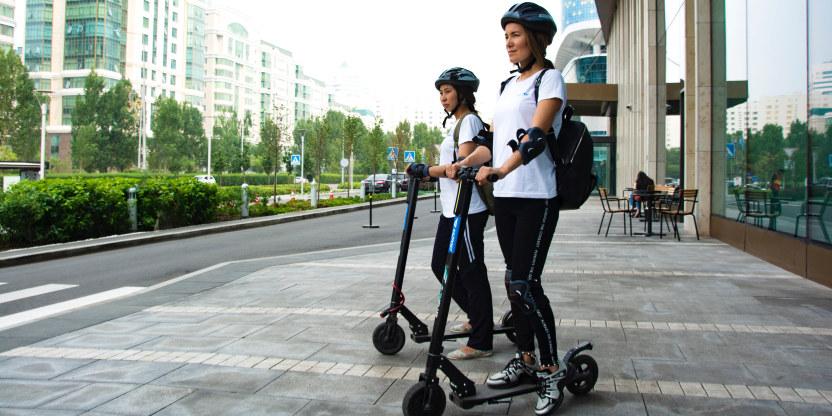 To kvinner på sparkesykler med hjelm