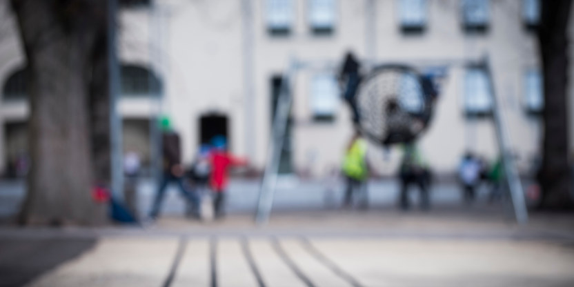 Uskarpt bilde av en skolegård med elever som leker.