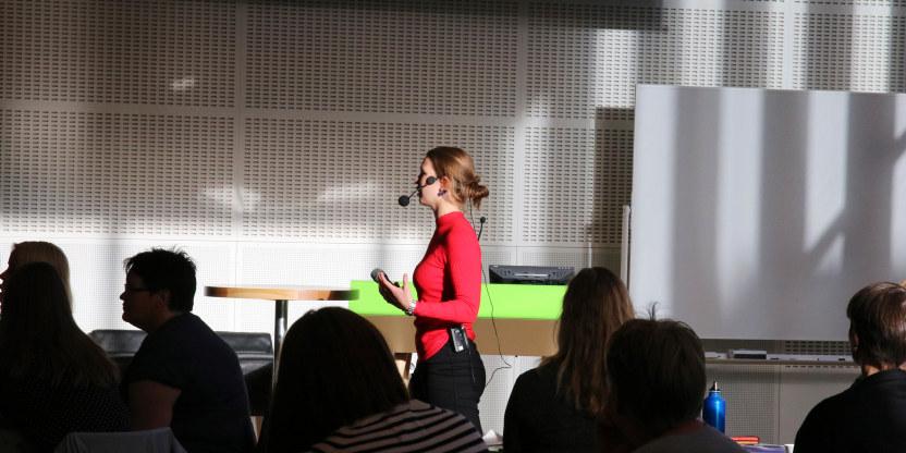 En ung kvinne i rød genser med mikrofonhodesett går rundt blant deltakere på et kurs.