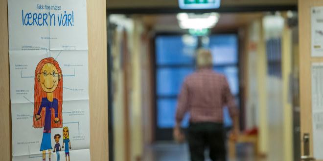 """En tilsynelatende sliten mann går ensom i en korridor med ryggen til. Bak ham henger en plakat på døra med teksten """"Takk for at du er lærer'n vår""""."""