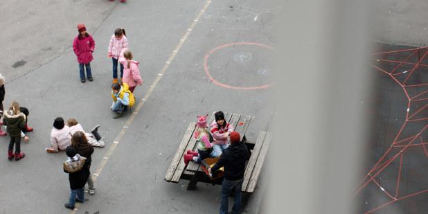 Bilde av barn på en skolegård tatt fra vindu over skolegården