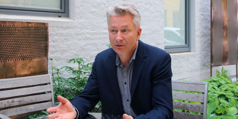 Tormod Korpås sitter ved et bord og snakker og gestikulerer.