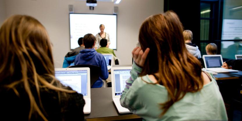 Elever som ser på en lærer foran en tavle