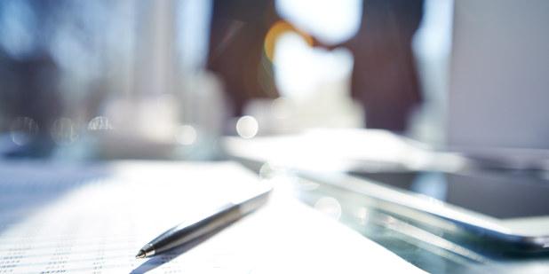 En penn ligger på et bord mens to personer gir hverandre et håndtrykk. Foto: Istock.